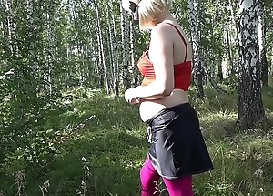 Concurrence with nature, a pregnant girl undresses in the forest, a public place outdoors.